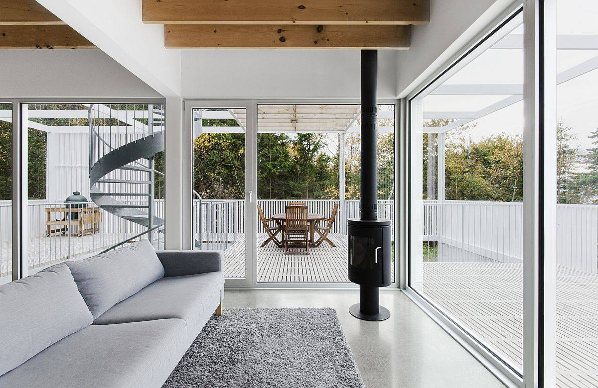 Lovely white living area of the house with glass walls and beautiful deck all around