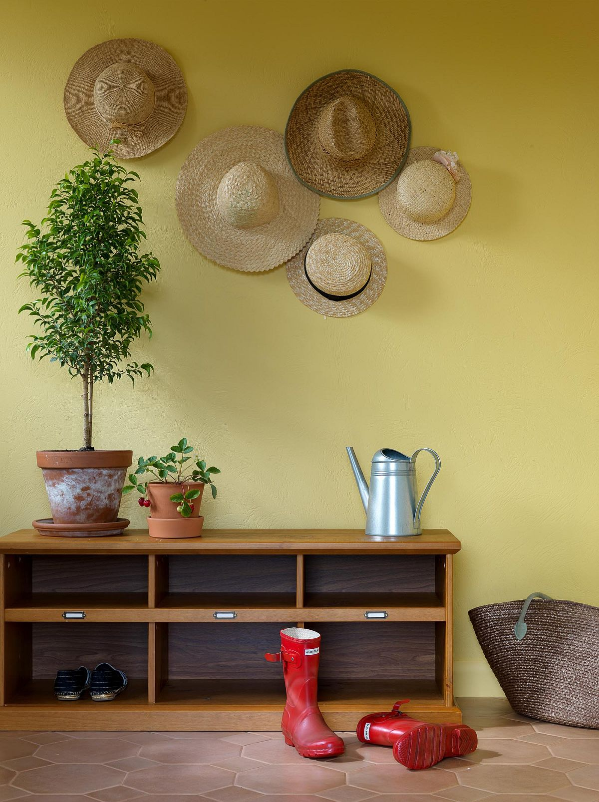 Mellow yellow accent wall for the contemporary entry wih space for boots and hats!