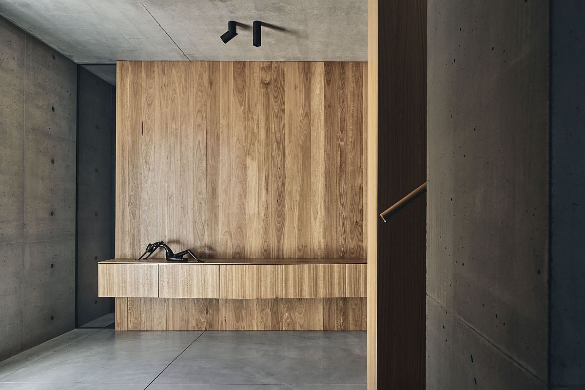 Minimal and modern entry of the home with concrete walls and wooden accents