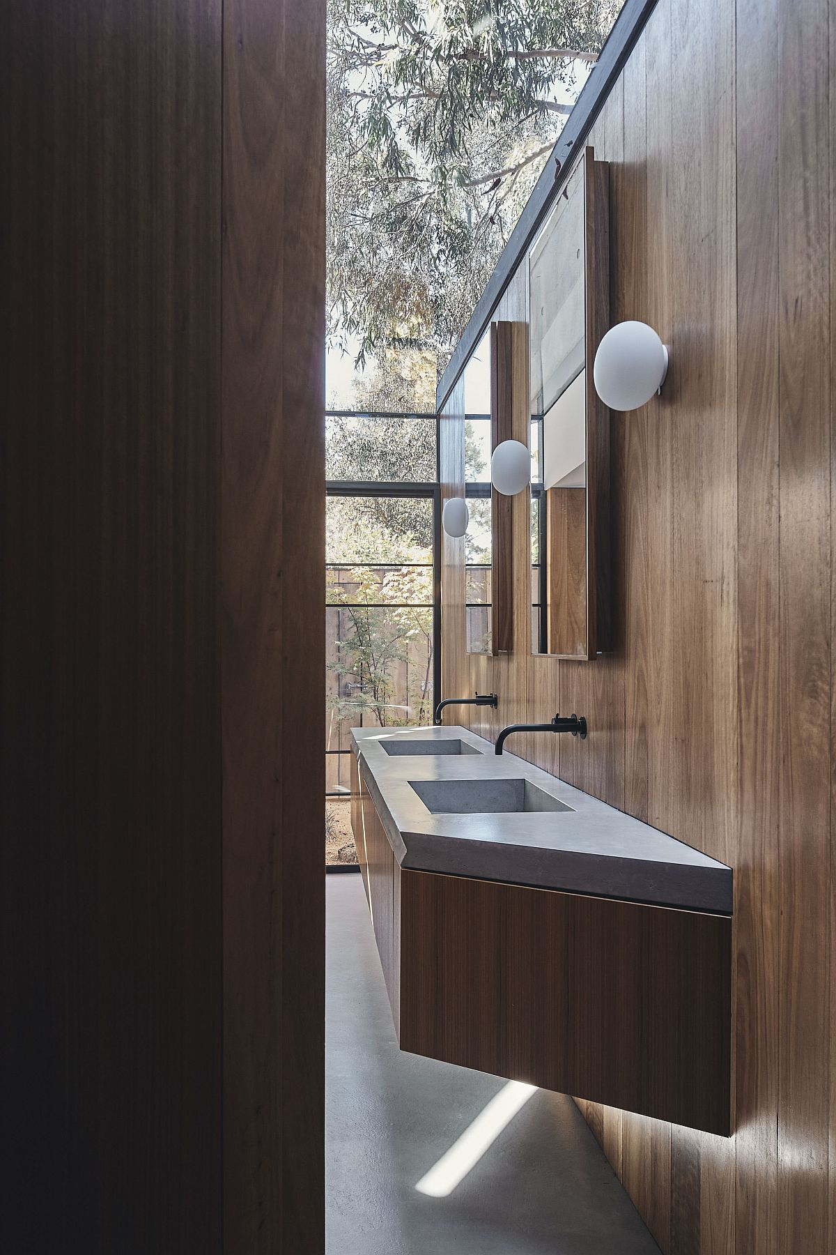Minimal bathroom of the house with floating wooden vanity and a view of the outdoors