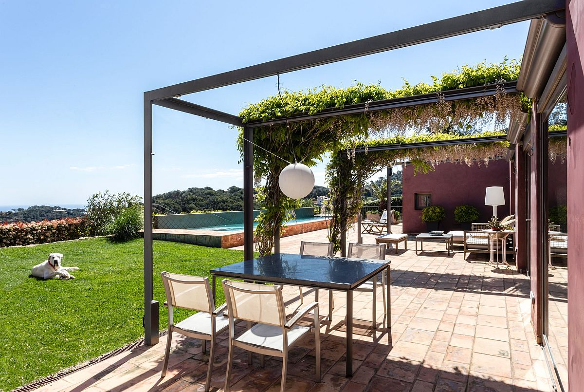 Minimal pergola frame is draped with greenery in an organic fashion