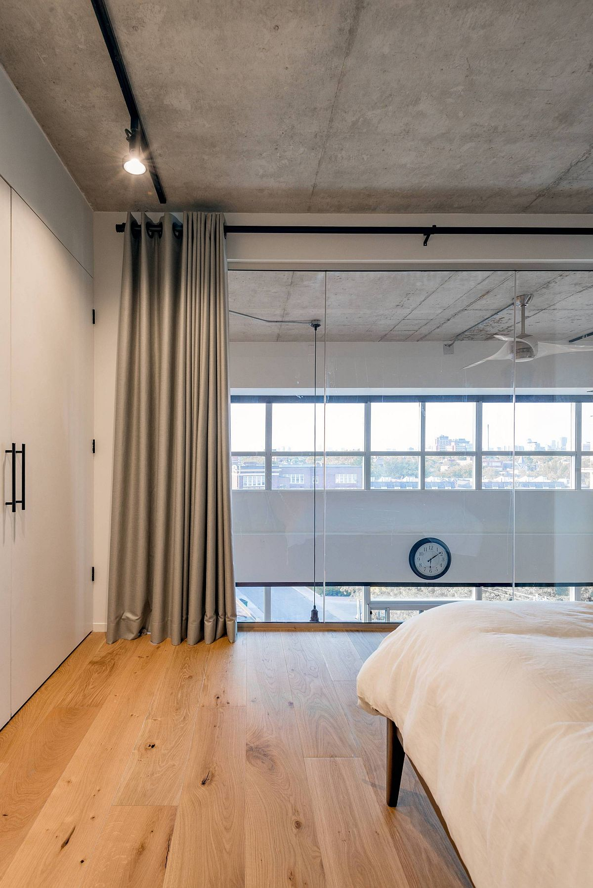 Modern bedroom with wooden floor, concrete ceiling and gray drapes
