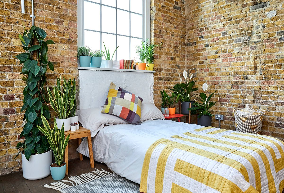 Modern industrial bedroom with brick walls and greenery all around