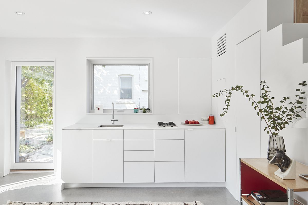 Modern, space-conscious kitchen in white inside small laneway house