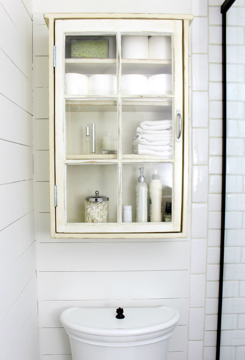 Old white cabinet full of things above toilet