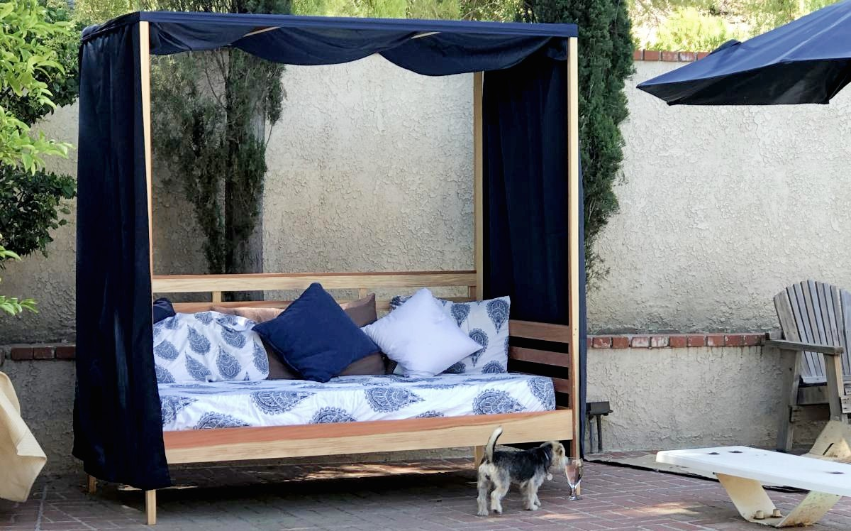 outdoor daybed with blue canopy and cushions