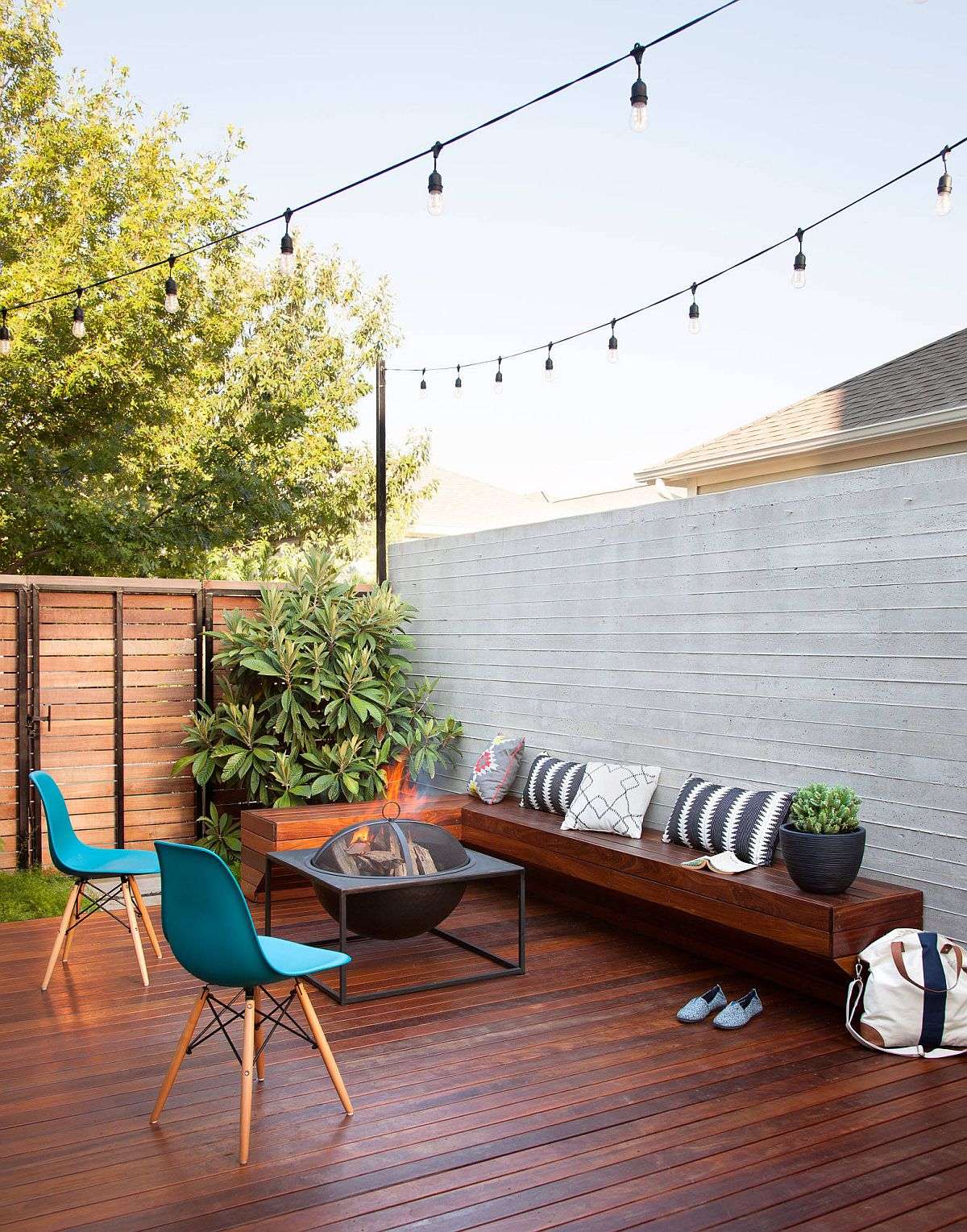 Private wooden deck design with fire pit, custom wooden bench and string lighting
