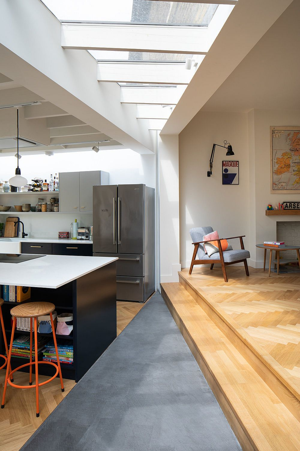 Raised level inside the home delineates the living area from the kitchen and dining space next to it in a subtle fashion