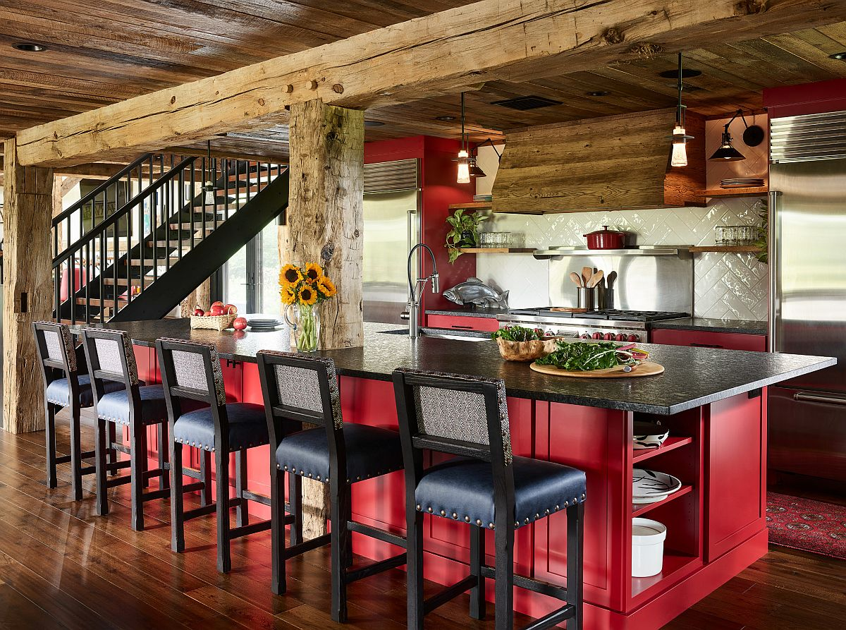 Red kitchen islands coupled with wooden cabinets in the spacious rustic kitchen