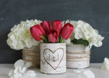 Red tulips in a carved vase in the middle of white flowers