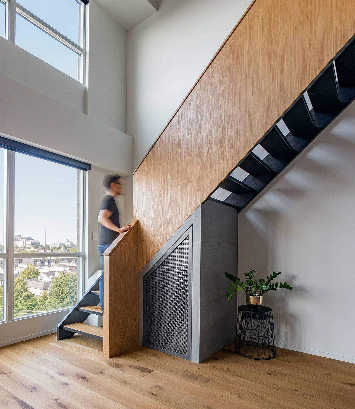 Revamped staircase in wood and metal connects the two levels of the loft home