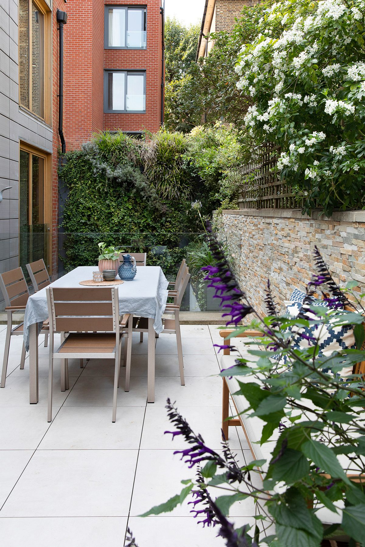 Small contemporary deck of London home with alfresco dining is surrounded by greenery