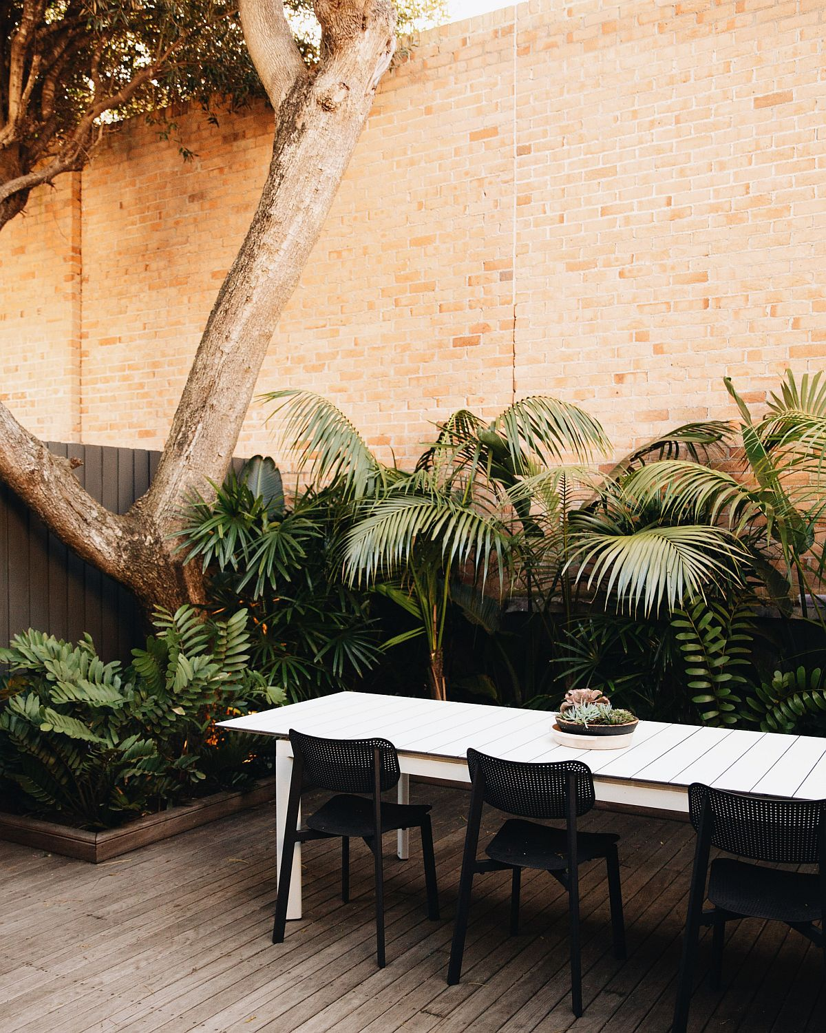 Small contemporary decor with brick wall backdrop and ample greenery all around