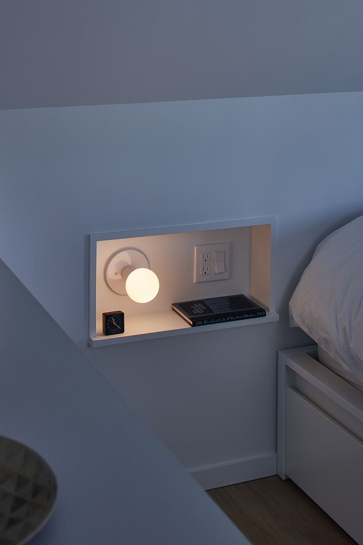 Small niche next to the bed inside the modern bedroom with space for a book and bed lamp
