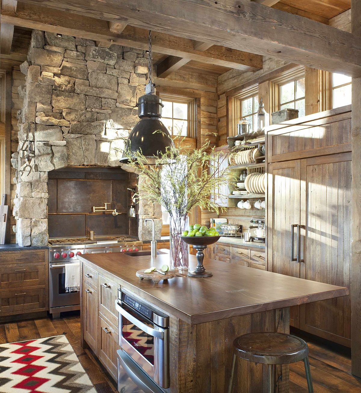 Spacious rustic kitchen with wooden countertops, cabinets and custom metal range