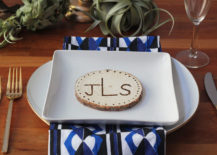 Table setting with wooden placecard on top of a white square plate