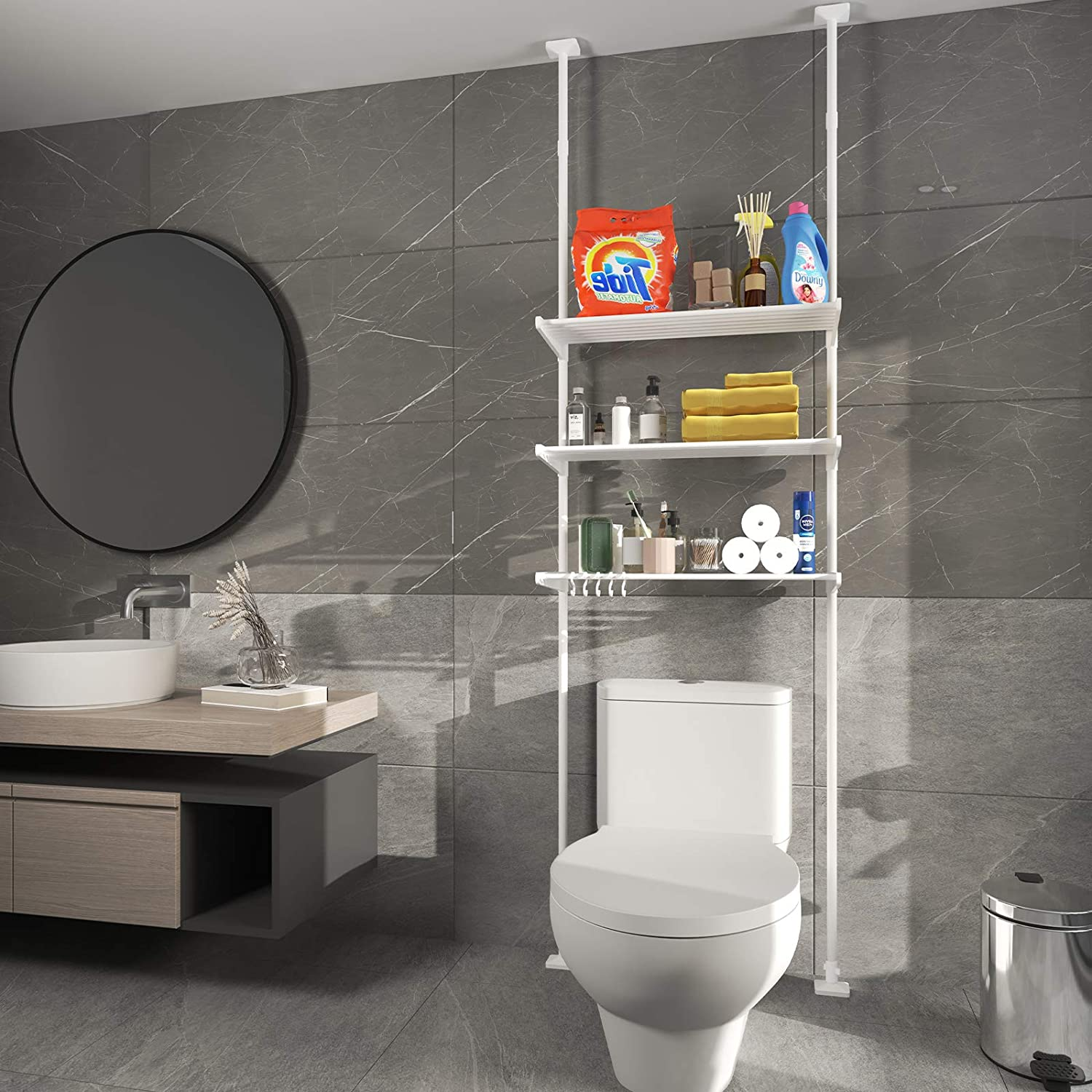 Three-layer adjustable shelf hooked from ceiling to wall in a gray tone bathroom with round mirror