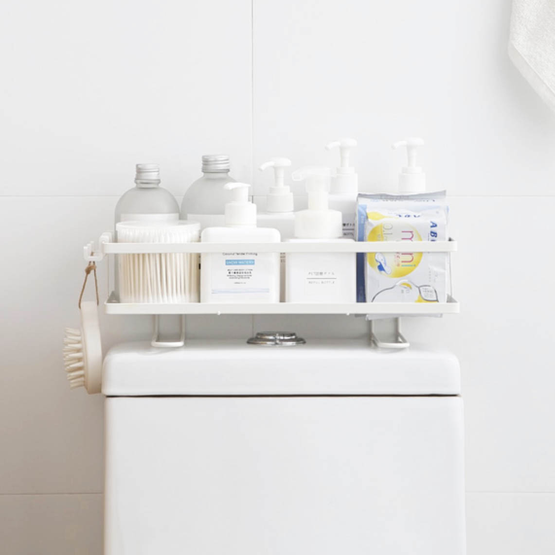 Toiletries in organizer rack placed on top of toilet