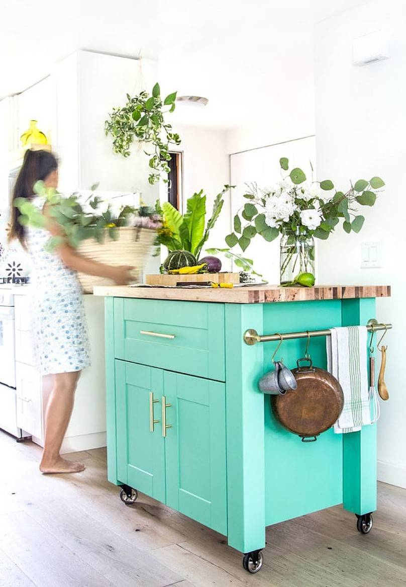 Utensils hanging on the side of green cabinet