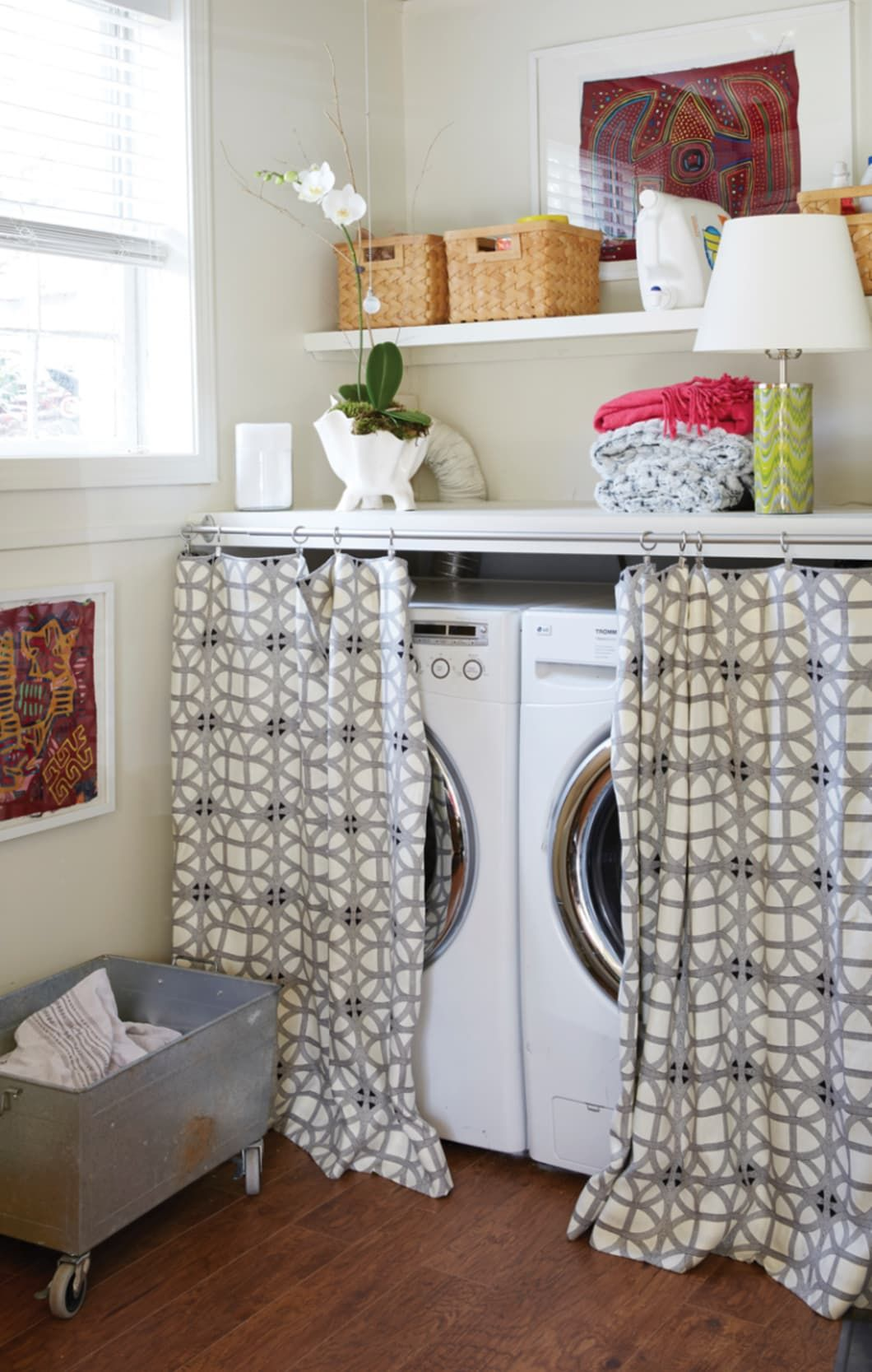 Washer and dryer hidden behind drapes and galvanized laundry cart