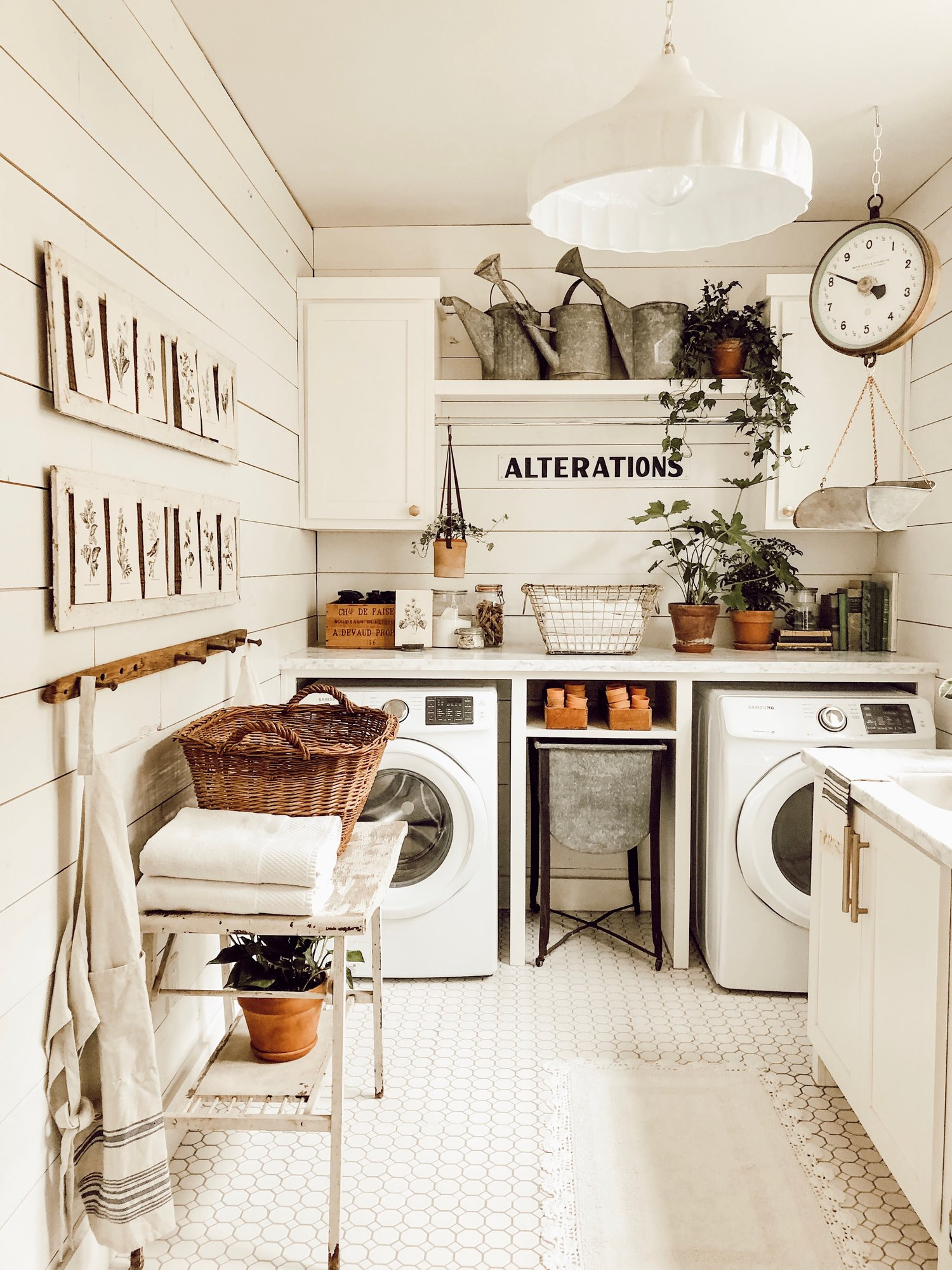 White laundry room with vintage decorations, plants and hanging weighing scale