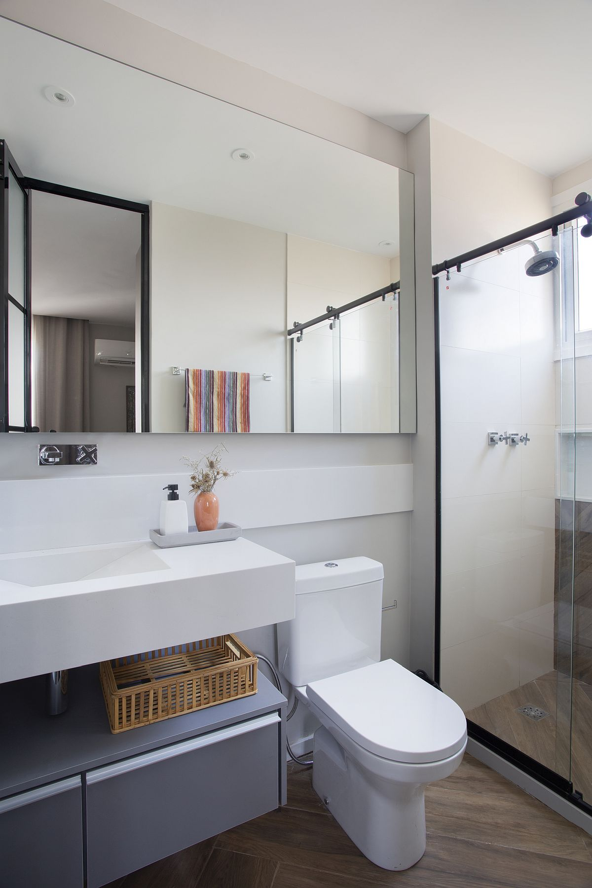 Wooden flooring coupled with gray and white touches in the small modern bathroom