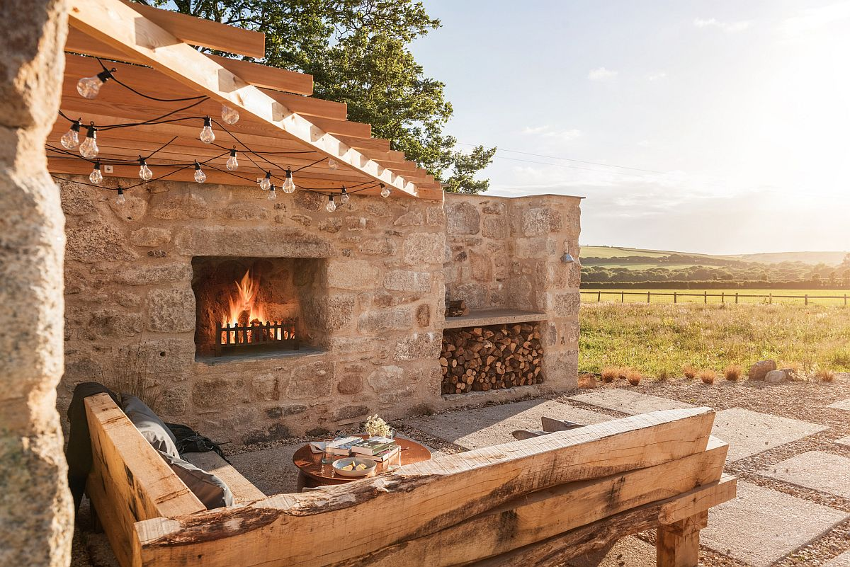 Wooden pergola structure coupled with stone walls create a relaxing and comfortable hangout outdoors