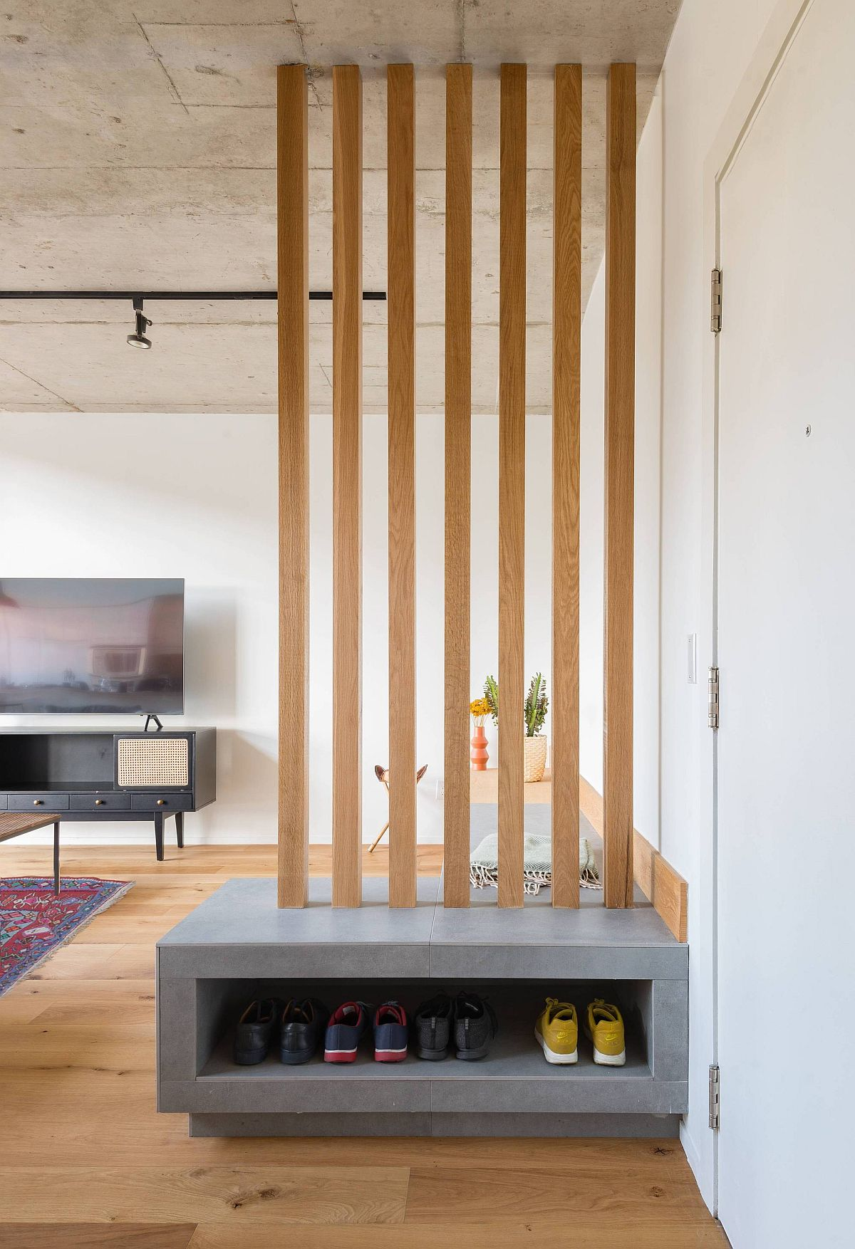 Wooden slats along with custom bench in the living room also offer shoe storage space for the entry