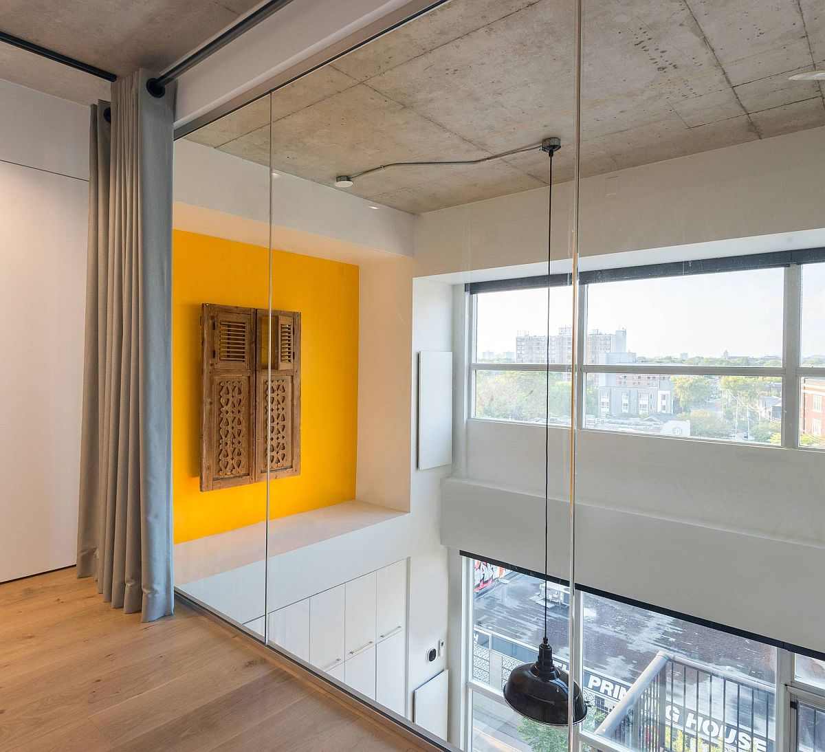 Yellow accent feature with reclaimed window shutters adds color to both the levels