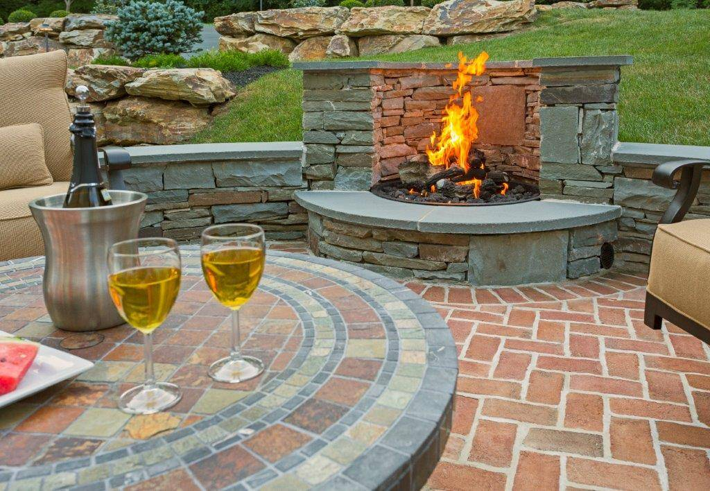 Large natural traditional stone and brick outdoor fire pit idea