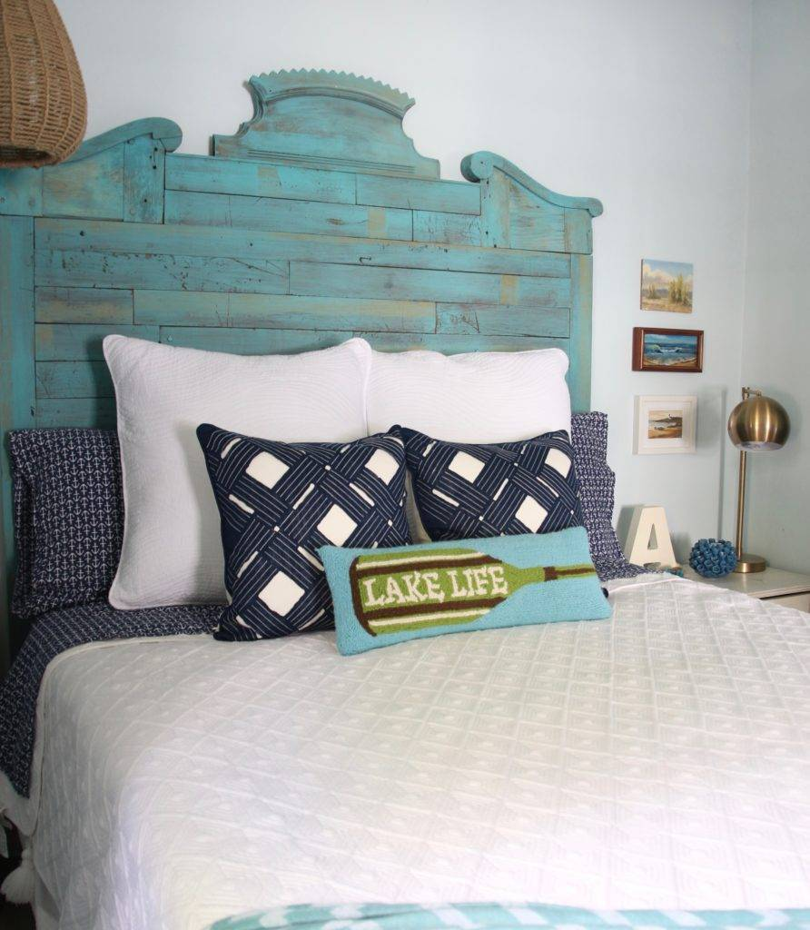 Bed with reclaimed headbord and blue and white pillows