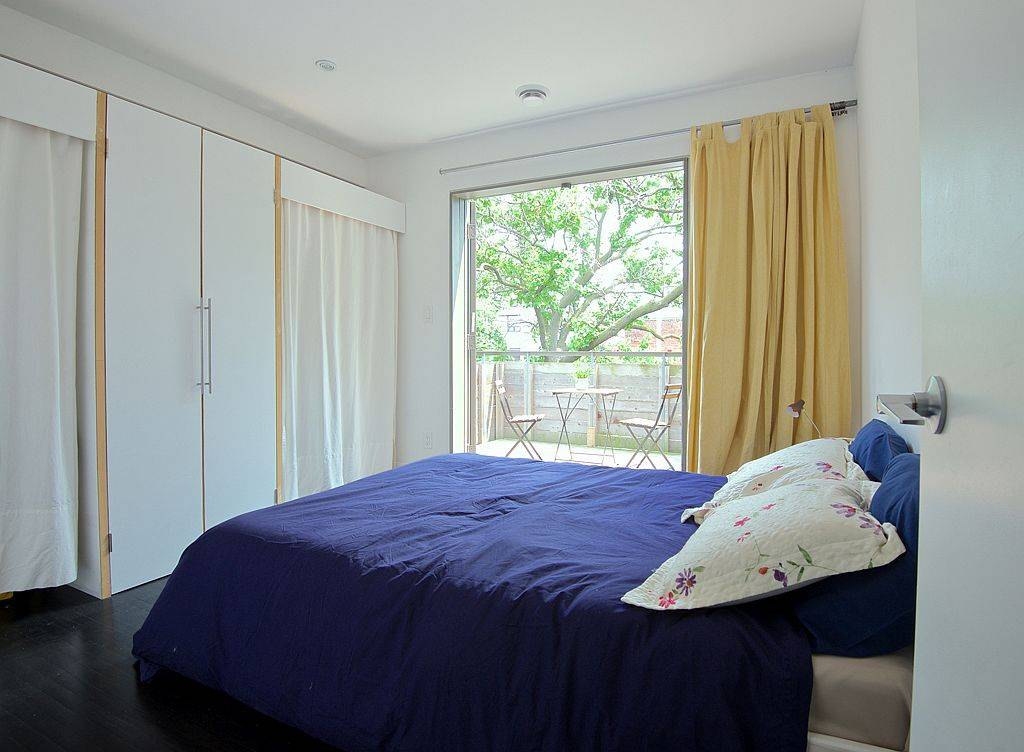 Bedroom in white with sliding glass doors accentuated by pops of yellow and blue