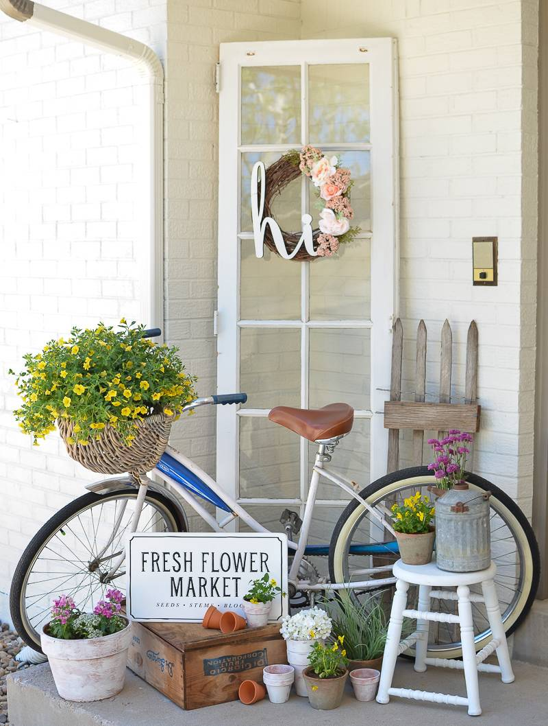Bike with basket of yellow flowers leaning against white wall