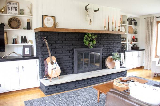 black painted brick fireplace with eclectic decorations