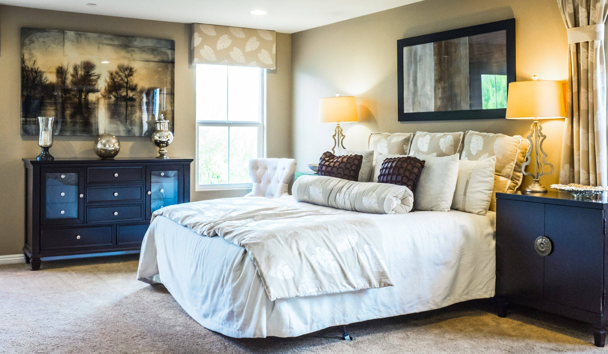 Blue drawers and side table in room with queen-size bed