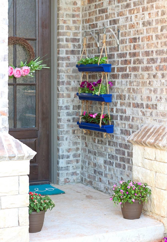 Blue hanging rain gutter planters on brick wall