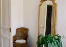 Chair and large gold mirror behind open door