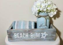 Coastal bathroom decor box with towel and white flower on mason jar