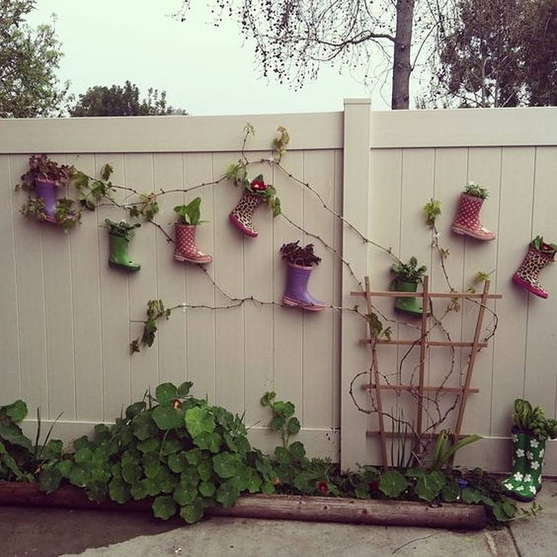 Colored boots hanging on white fence with vines
