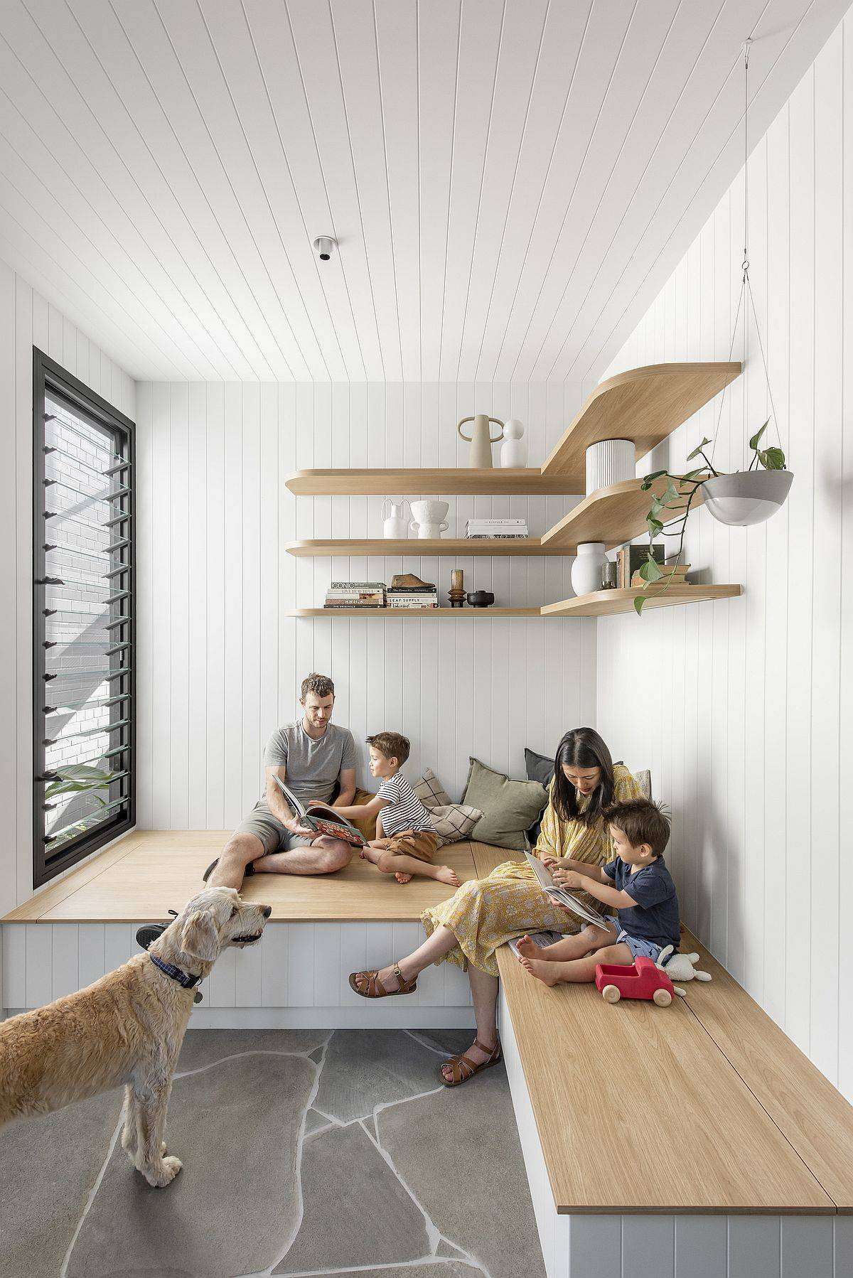 Custom wooden bench with storage and floating wooden shelves for the family room