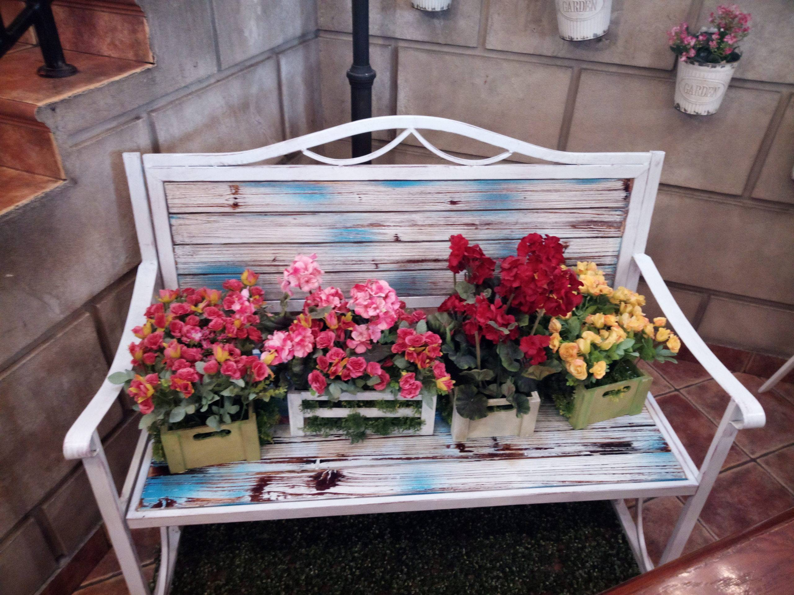 Flowers in square boxes on top of white bench