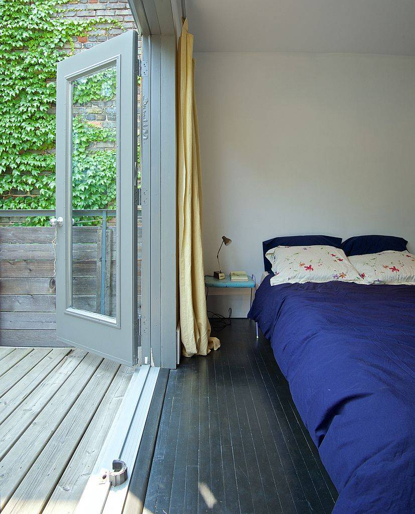 Folding glass doors swing open to connect the bedroom with the deck