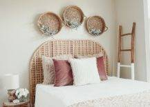 Half-painted wood ladder beside a bed with three wicker baskets above