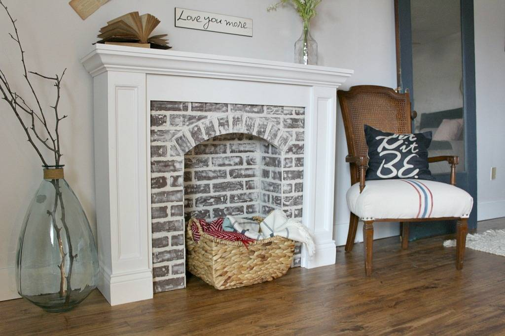 faux brick fireplace with basket of blankets in surround
