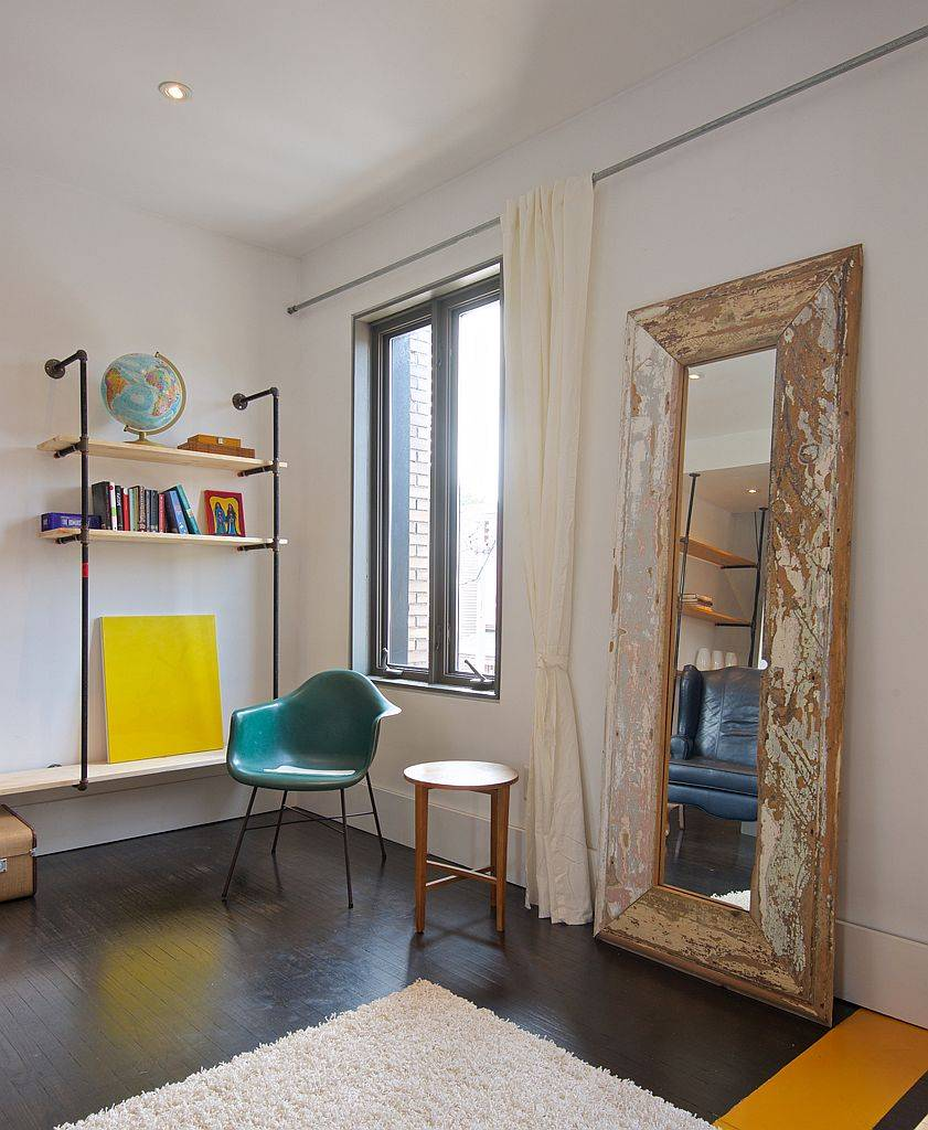 Large mirror with wooden frame on the floor is used as a decorative piece in the living room