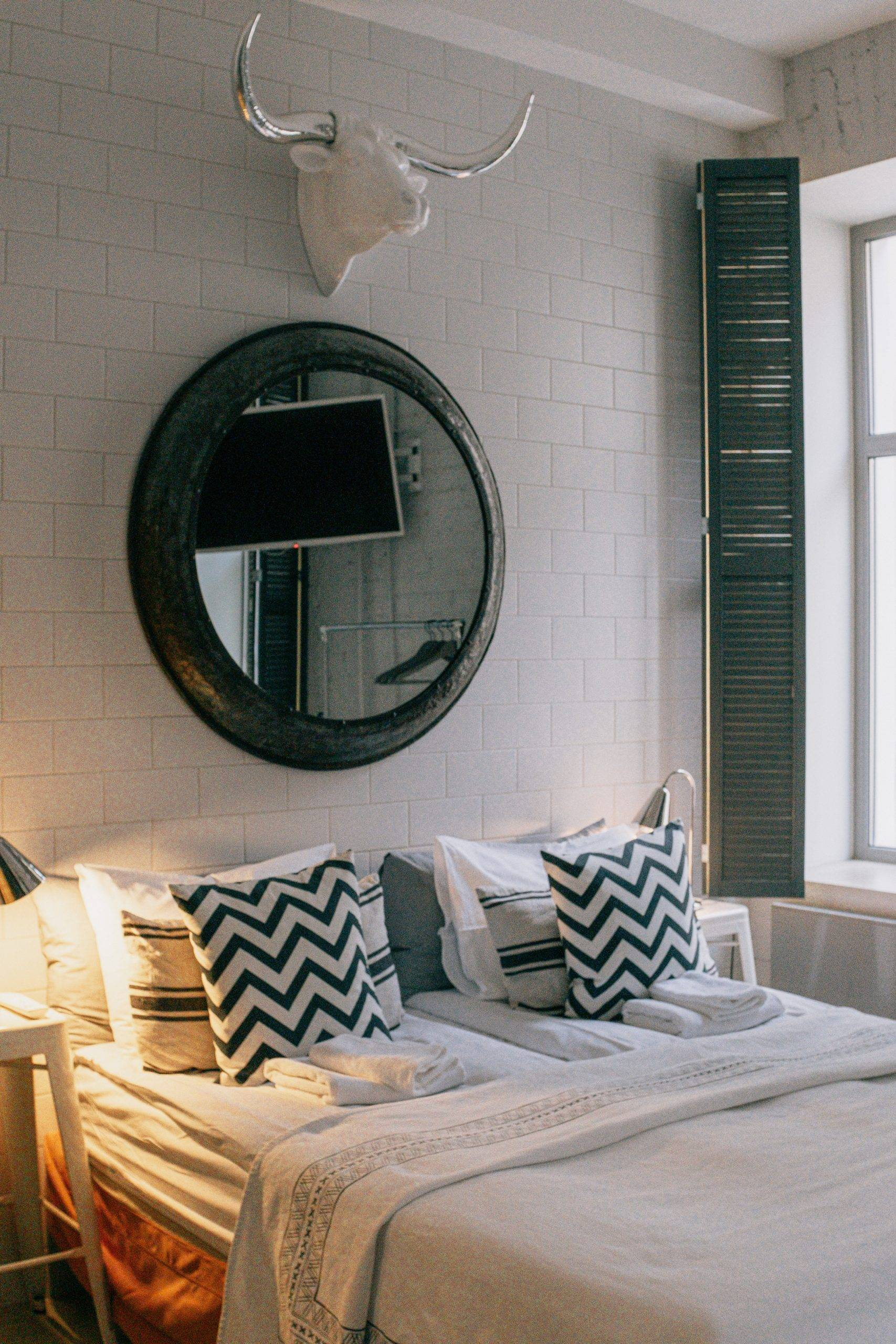 Large round mirror and bull head on the wall above the bed