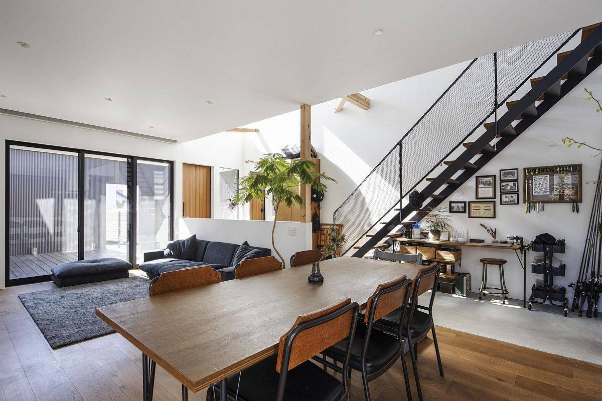 Light-filled living area and dining room of the home in white, gray and wood