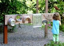 Little girl in blue facing different metal wares hanging on a wood