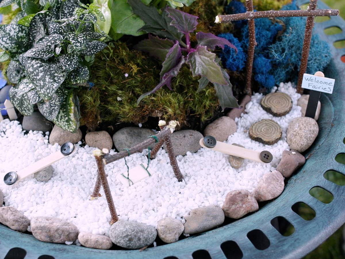 Miniature swing and slides on top of white pebbles surrounded by plants