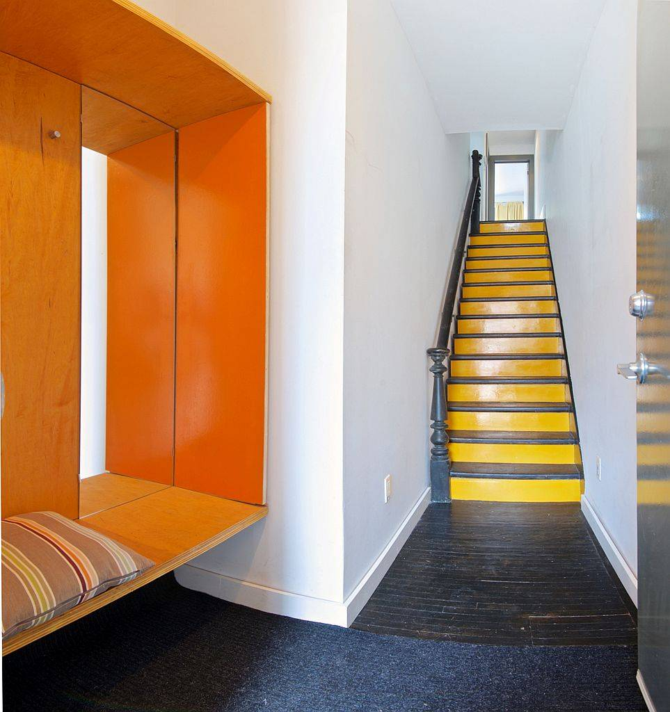 Modern entry with bench and a colorful splash of orange inside the Toronto home